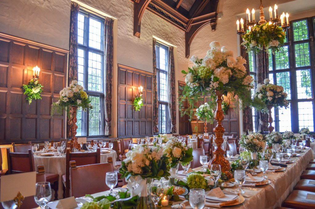 Grand room tables setup for dining adorned with flowers