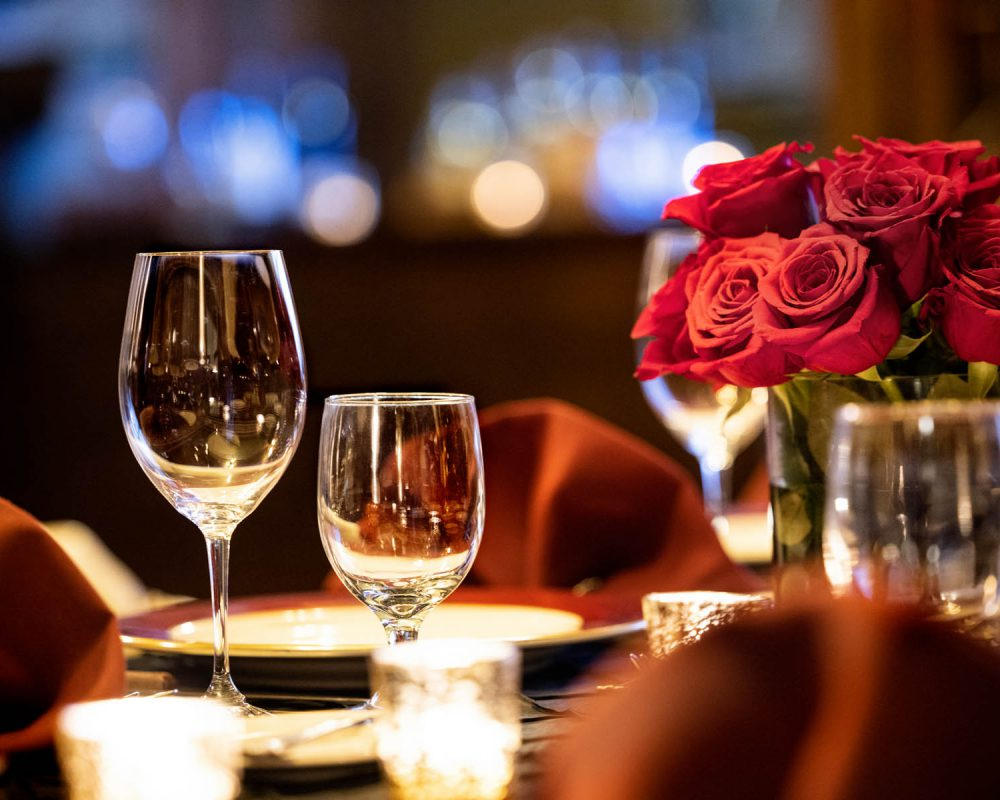 Wine glasses with roses on a dining table
