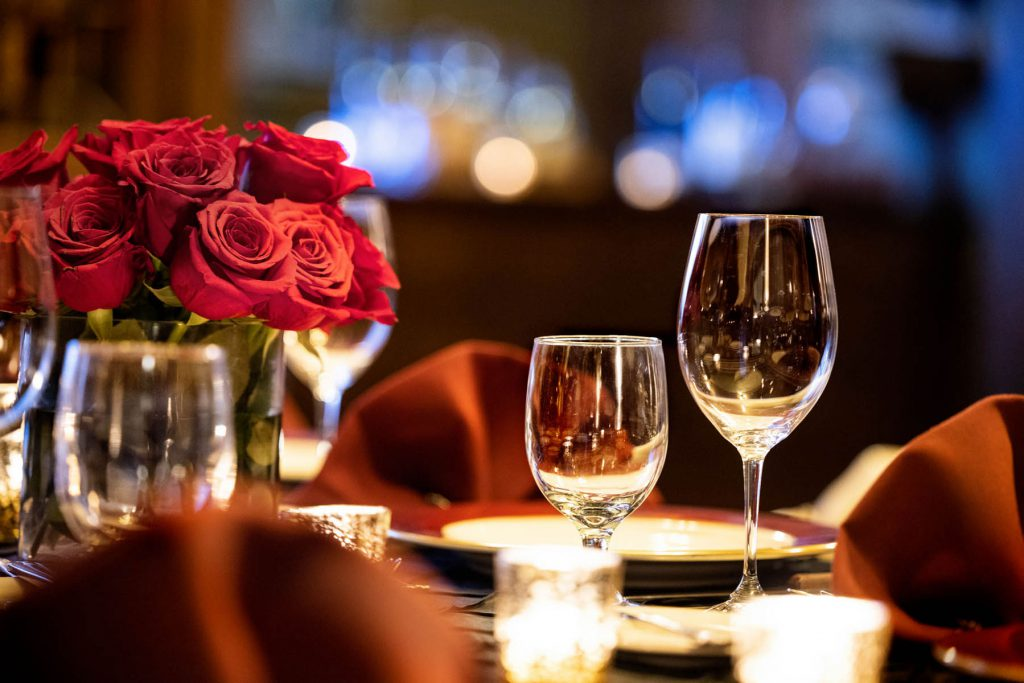 Wine glasses and roses on a dining table