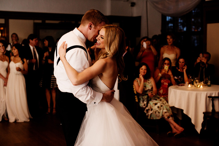 bride and groom dancing together in a room full of friends